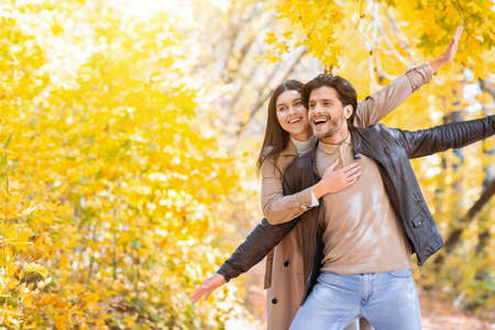 Happy lovers hugging and imitating airplane, enjoying time together in autumn forest, free space Stock Photo