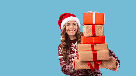 Xmas shopping. Lovely girl in warm sweater and Santa hat holding stack of gift boxes on blue background, copy space. Panorama