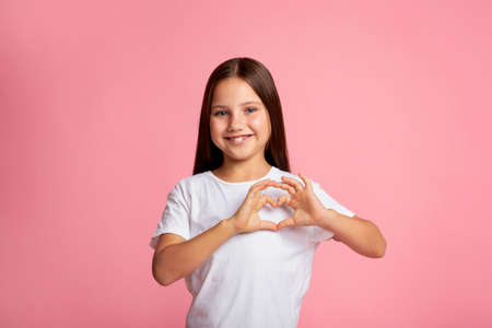 Expression of emotion of love and kindness. Smiling little girl showing heart sign with hands, isolated on pink background, studio shoot