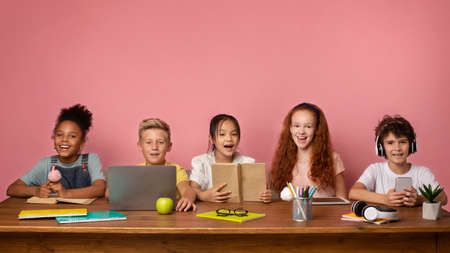 Remote schooling. Group of boys and girls with learning materials and devices sitting at desk over pink background, free space. Panorama