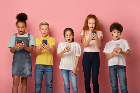 Shocked schoolkids looking into their mobile phones over pink background