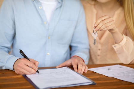 Cropped view of young couple with house key signing real estate purchase agreement at table, closeup Фото со стока