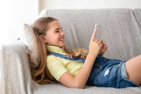 Everyday Life Concept. Side view of laughing teenage girl using her smart phone, lying on the couch in bedroom Stock Photo