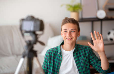Teen blogger shooting video for his suscribers from home, waving at camera