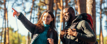 Panoramic photo of two multiracial backpackers man and woman enjoying forest views, girl pointing aside, panorama