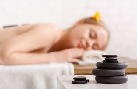 Pile of massage stones for spa, close up. Girl with closed eyes and hot stones on back, soft background, free space