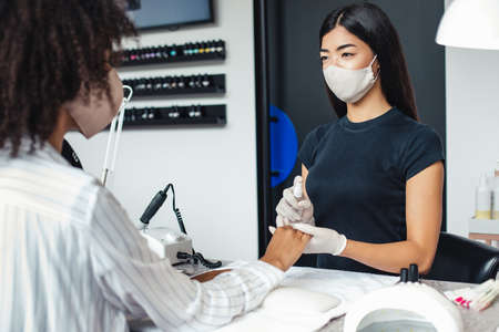 Manicure and pedicure salon, coronavirus, covid-19, social distance concept. Asian girl in protective mask disinfects nails to african american client in studio interior