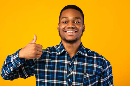 Positive African Man Gesturing Thumbs-Up Approving Something Smiling To Camera Standing Over Yellow Background. I Like It. Studio Shot