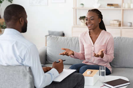 Happy african woman talking with psychologist at private therapy session, sharing her progress, sitting on couch and smiling, free space Stockfoto