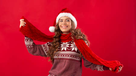 Cheerful young girl wearing cool Christmas outfit on red background, panorama