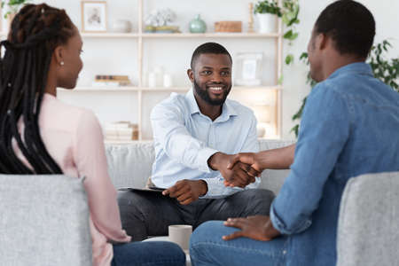 Marriage Counseling. Thankful Black Couple And Marital Therapist Shaking Hands After Successful Meeting In Office, Selective Focus