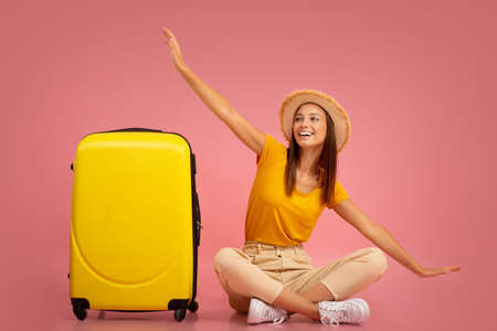 Happy girl in hat sitting next to suitcase, imitating airplane, excited about her vacation, pink studio background