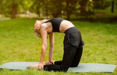 Strength yoga routine. Flexible young girl doing camel pose on fitness mat outside