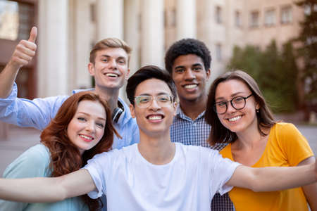 Cheerful Multicultural Students Posing Together Making Selfie Near University Building Outdoors. College Education Concept