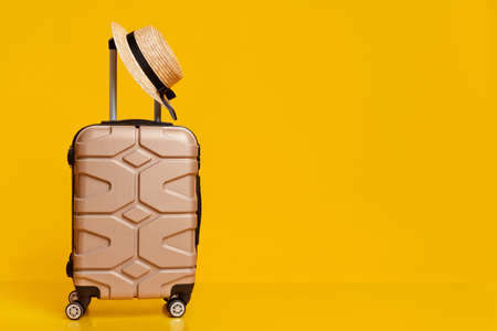 Travel Concept. Hand luggage suitcase with hat on it over yellow studio background with copy space