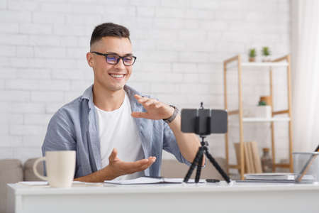 Work and study online during self-isolation. Man in glasses gestures and looks at camera of smartphone in interior of living room