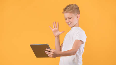 Hi There. Preteen guy using tablet webcam for video chat and waving with hand, orange wall