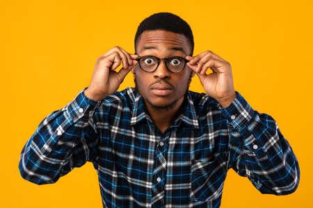 Eyesight Correction. Amazed African American Looking At Camera Through Eyeglasses Standing Over Yellow Studio Background. Reklamní fotografie