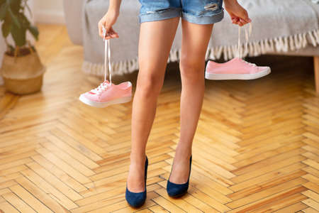 Unrecognizable girl wearing high heels shoes and holding pink sneakers, standing in living room