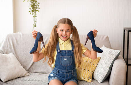 Portrait of a joyful little girl holding pair of high heels shoes, sitting on couch in living room
