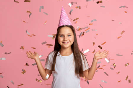 Childhood, mood and emotions. Smiling little girl enjoy confetti on birthday on pink background, studio shoot