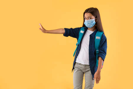 Dont Get Close To Me Concept. Cautious pupil wearing medical mask showing stop hand gesture, pastel orange studio wall 写真素材