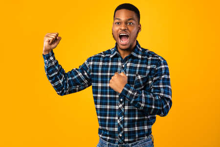Black Guy Shouting Loudly Beating His Chest Standing Over Yellow Background Posing In Studio
