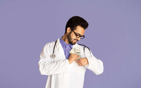 Corruption in healthcare concept. Indian doctor putting money into his pocket on lilac background, panorama