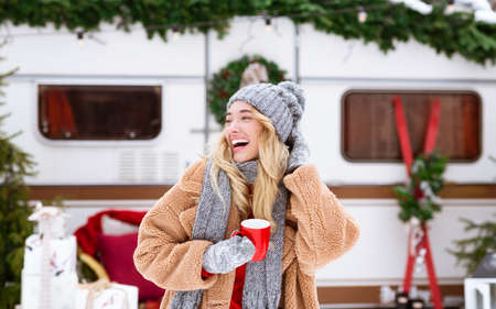 Winter Camping. Happy laughing girl enjoying cup of tea near campervan outdoors, wearing coat, hat and scarf, enjoying seasonal holidays and leisure