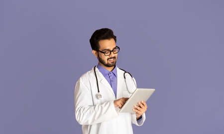 Handsome Indian doctor with tablet computer giving online consultation to patient over lilac background, panorama