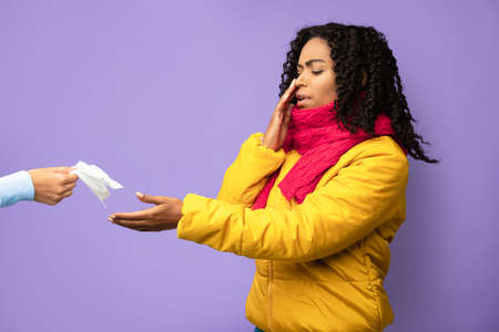 African American Girl Suffering From Nose Bleeding Taking Tissue To Stop Blood Standing On Purple Studio Background. High Blood Pressure