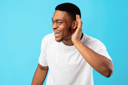 I Dont Hear You. Black Man Listening Holding Hand Near Ear Standing Over Blue Background. Studio Shot