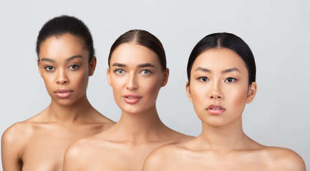 Three Diverse Women Posing Naked Standing In Studio On Gray Background, Looking At Camera. Multicultural Beauty Concept. Panorama