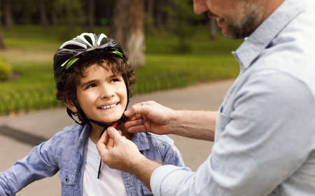 Safety First. Closeup of father putting protection helmet on his little son at park, outdoor shot