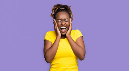 Emotional african girl with closed eyes touching her face and screaming, expressing happiness, purplr background, panorama