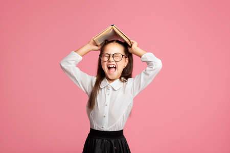 Oh no, i hate to study. Schoolgirl in uniform and glasses screams and holds book on her head, isolated on pink background