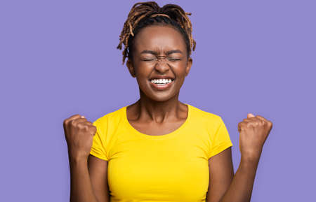 Black girl celebrating great success over purple background, clenching fists