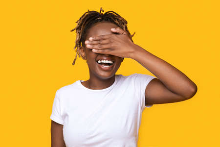 Happy black girl covering her eyes, excited woman on yellow background 스톡 콘텐츠