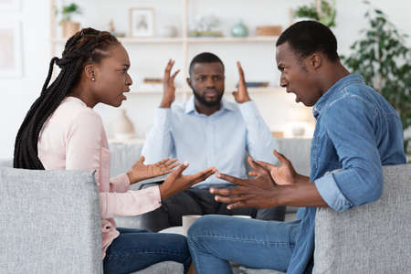 Marriage Therapy. Shocked Family Counselor Overlooking Black Couple Emotionally Arguing At His Office, Screaming At Each Other, Selective Focus