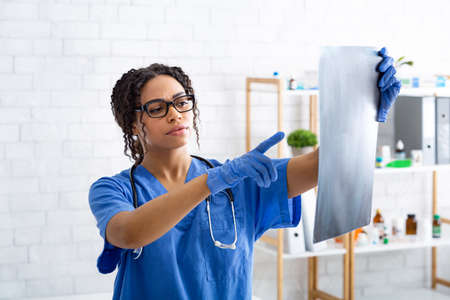 Thoughtful female radiologist looking at animal xray in veterinarian hospital