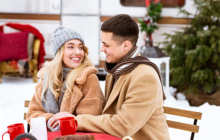 Romantic Date At Camping. Loving Young Couple Drinking Hot Tea Outdoors At Winter Campsite, Having Coffee In Red Mugs, Smiling And Looking At Each Other With Love, Enjoying Christmas Holidays Together