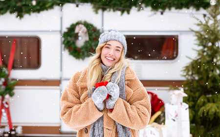 Winter Fairy Tale. Smiling Blonde Woman Drinking Hot Tea Outdoors And Looking At Snowfall, Enjoying Cold Season Camping And Travel During Christmas Holidays, Modern RV On Background, Copy Space