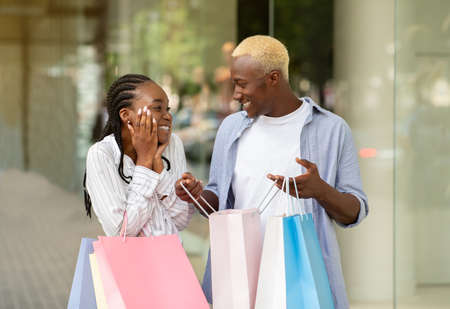 Cheerful african american guy shows purchases in bag, expressing happiness to girl near shop window, free space