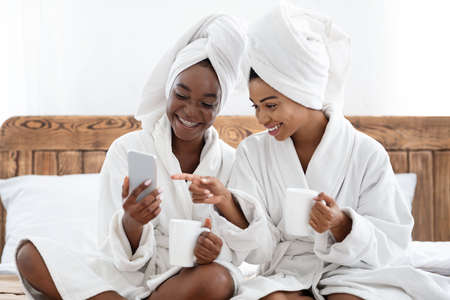 Two happy black women in bathrobes and towels on their heads drinking coffee and using smartphone. Cheerful african american girlfriends having fun at home, using beauty mobile application, free space Standard-Bild