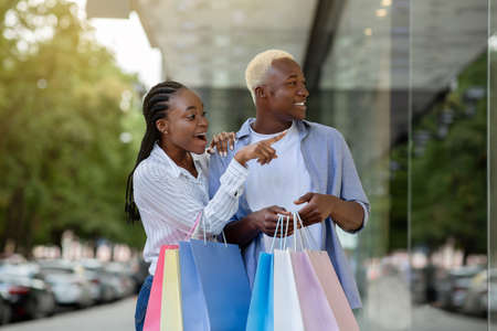 Surprised african american guy and girl saw original thing in shop window, copy space