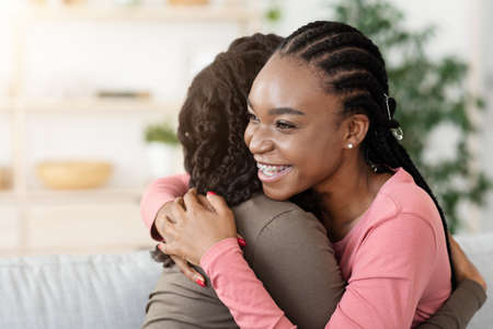Pretty african american girlfriends hugging at home, happy to meet each other, copy space