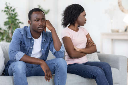 Relationships problems. Upset black man and woman sitting on couch at home, copy space