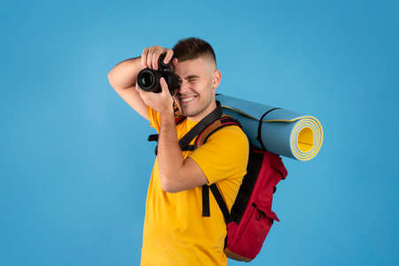 Cheerful young traveler with backpack and camera ready to take photos on blue background