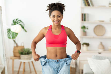 Joyful Slim Black Girl Wearing Old Big Jeans Showing Result Of Losing Excess Kilograms Standing Indoors, Smiling To Camera. Dieting And Slimming Motivation Concept