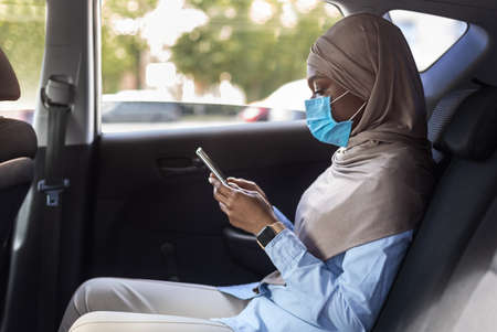 Black muslim businesswoman in hijab wearing medical protective mask on backseat of car and holding her smartphone, using taxi during coronavirus quarantine, following protective measures and distance